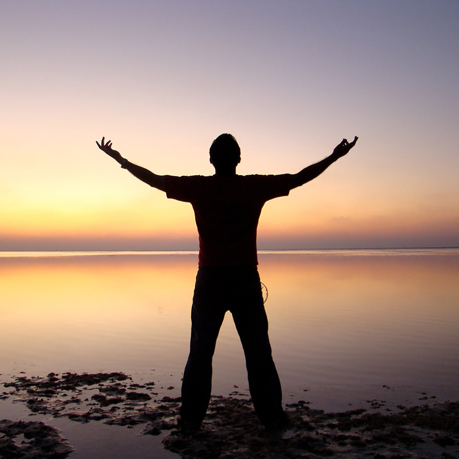 certification program man with arms raised facing sunset