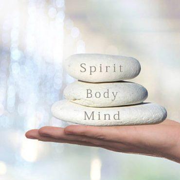 stones in hand that say spirit body mind